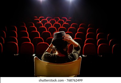 Young woman on director's chair on stage, in front of empty seats