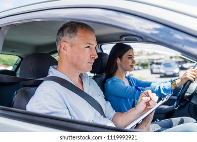 Young woman on a driving test with her instructor. Learning to drive a car. Driving school. Instructor of driving school giving exam while sitting in car