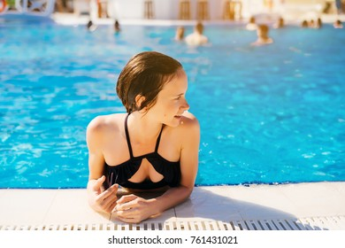 Young woman on the edge of the swimming pool looking around