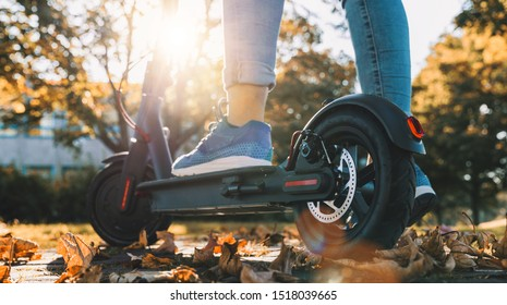 young woman on the electric scooter on the road in autumn at sunset