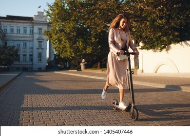 young woman on electro scooter in city. woman riding scooter in sunset light in street