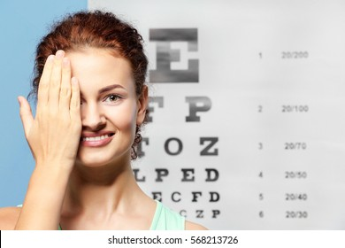 Young woman on eyesight test chart background