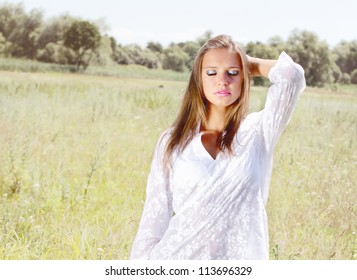 Young woman on the field with flowers