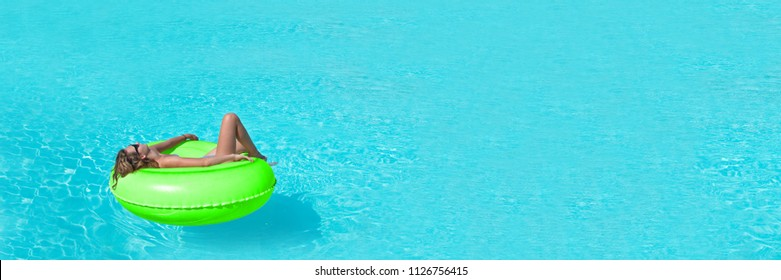Young woman on giant inflatable swimming ring relaxing in swimming pool, panoramic summer and vacations concept