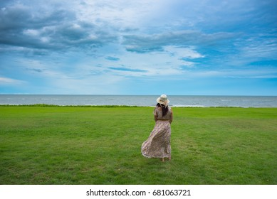 young woman on the grass with cloudy sky.using as travel and relaxing concept