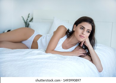 Young woman on her bed wearing white underwear. She is leaning on her hand and looking away.