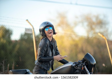 Young woman on her motorcycle with helmet , glasses of aviator and mobile phone smiling and happy at sunset. concept of technology and lifestyle in freedom