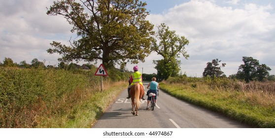Young woman on a horse and woman on cycle enjoy a walk down quiet country roads in rural england.