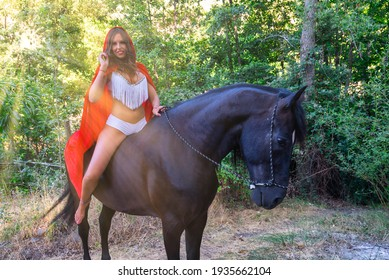 Young woman on horseback with sunlight, red cloak and fashionable bikini. Little red riding hood. High quality and high resolution photography.