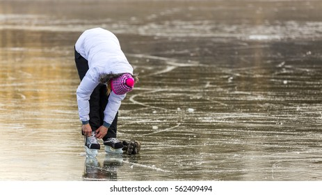 Young woman on ice skates fit the frozen lake. In Hungary, the winter outdoors.