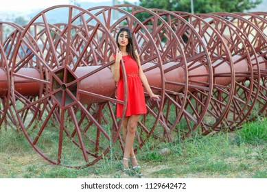 Young woman on industrial red background-large empty spools of electric cable.Beautiful female manager at electrical wire and cable factory. Brunette serious girl standing outdoor wearing red dress.