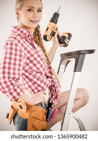 Young woman on ladder with toolbelt using driil and some power tools for her work at home. Girl working at flat remodeling. Building and renovation.