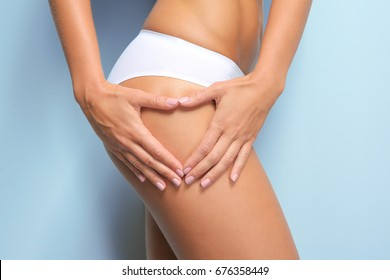 Young woman on light background. Cellulite problem concept