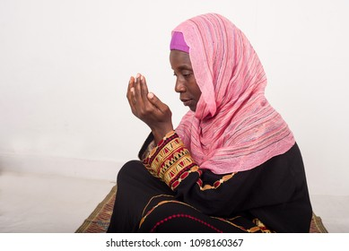 young woman on matted veiled head and praying.