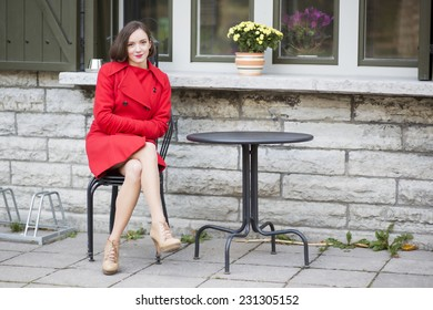 Young woman on metal chair at street cafe