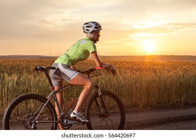 Young woman on the mountain bike. Girl riding bicycle on the road at beautiful sunset. Walk on the bike in nature.