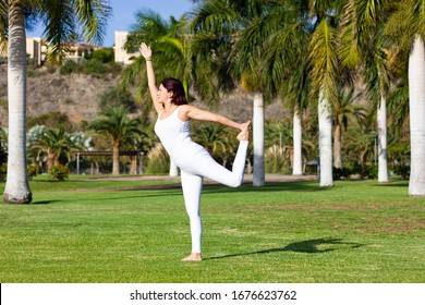 Young woman on natarajasana in the park. Female yogi practices lord of the dance yoga pose, with one arm extended forward and the other one lifting back leg up on natural environment