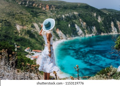 Young woman on Petani beach Kefalonia, admiring highly excited picturesque panorama of emerald blue bay of Mediterranean sea and steep coastline hills. Greece