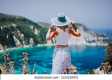 Young woman on Petani beach Kefalonia, holding blue sunhat enjoying picturesque panorama of emerald azure bay lagoon surrounded by steep cliff coastline. Greece