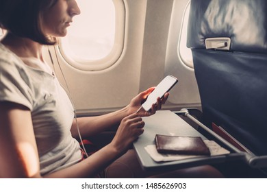 Young woman on a plane with a smartphone in her hands