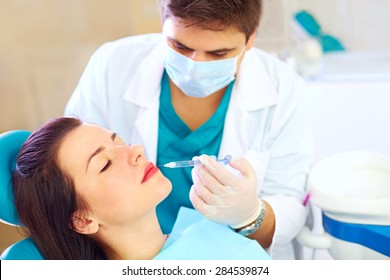 young woman on rejuvenation procedure in beauty clinic, filler injection