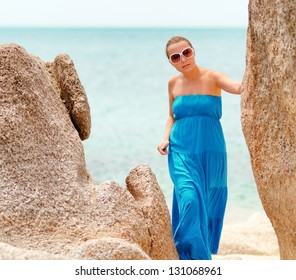 Young woman on a rocky beach.