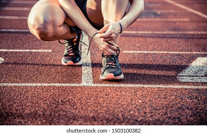 young woman on running track lacing her shoes