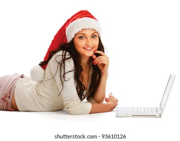 Young woman on santa hat lying on the floor with laptop, isolated on white background