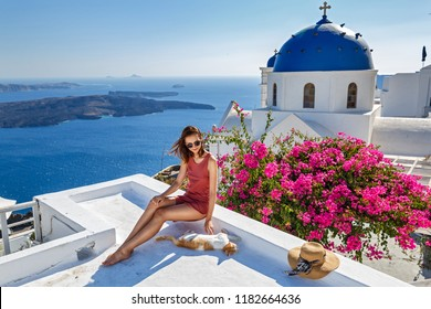 Young woman on Santorini island and red cat