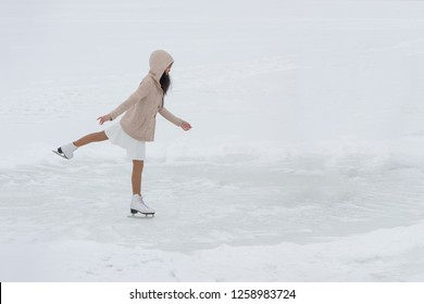 Young woman on skates in hood outdoors at snow