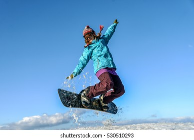 Young woman on the snowboard jumping