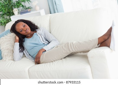 Young woman on sofa putting her feet up