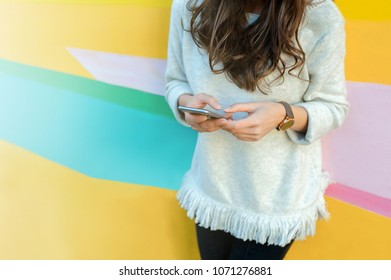 Young woman on the street holding a smartphone.