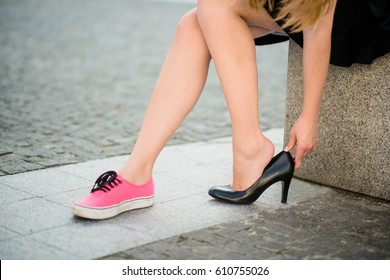 Young woman on street - one foot in sneaker other in high heel