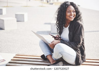 Young woman on the street working on laptop and talking on mobile phone.