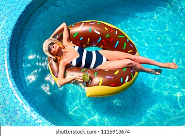 Young woman on summer pool party in swimming pool drinkig lemonade