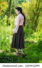Young woman on a summer sunny day walking and dancing in the forest with tall grass.