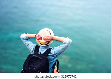 young woman on summer vacation, hiking on coastline and staring at sea wearing hat and backpack. Travel and adventure concept