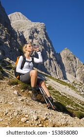 Young woman on a sunny day hiking in high mountains drinking water