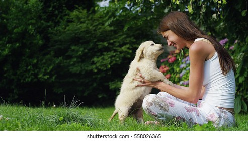 A young woman on a sunny day playing with his Golden Retriver puppy in the garden giving himself kisses with love and affection