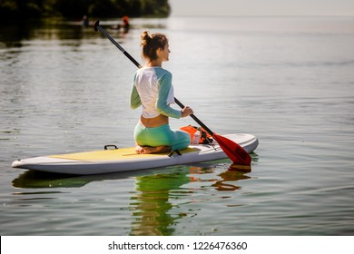 Young woman on sup board with paddle on summer day