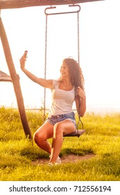 Young woman on a swing on a sunny autumn day. She is making selfie.