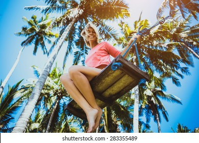Young woman on the swings between palms look to the camera and smile. Paradise conception