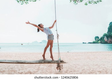 Young woman on swings on a sea beach