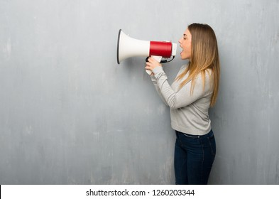 Young woman on textured wall shouting through a megaphone to announce something in lateral position