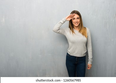 Young woman on textured wall saluting with hand