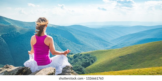 Young woman on the top of mountain