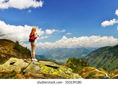 young woman on top of mountain,  background  of sky and clouds
