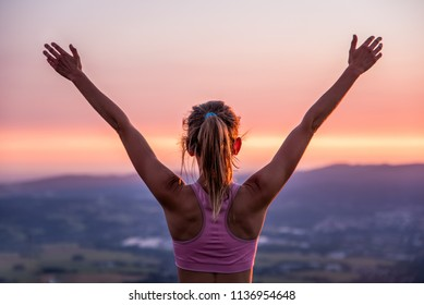 Young woman on top of the moutain at sunset with the arms raised enjoying freedom, Winner.