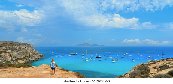 Young woman on the top of the rock cliff looks at paradise clear torquoise blue water with boats and cloudy blue sky in background in Favignana island, Cala Rossa Beach, Sicily South Italy.